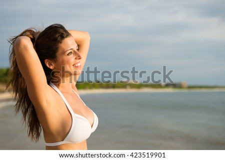 Relaxed woman at caribbean tropical beach enjoying summer vacation. Beautiful girl in white bikini on travel to Riviera Maya, Mexico.