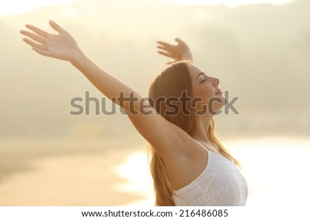 Relaxed woman breathing fresh air raising arms at sunrise with a warmth golden background - stock photo