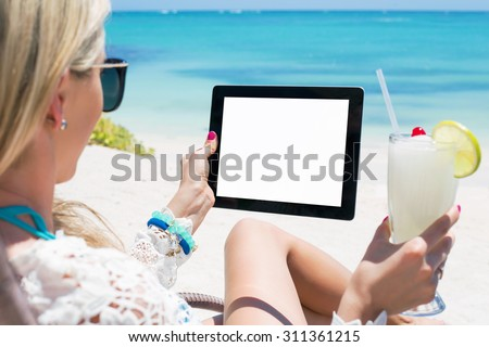 Relaxed woman drinking cocktail and holding tablet computer on the beach - stock photo