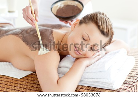 Relaxed woman enjoying a mud skin treatment in a Spa center - stock photo