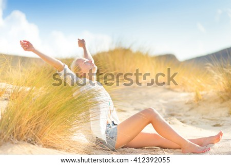Relaxed woman enjoying freedom and life in beautiful natural environment. Blissful girl raising arms, feeling free, relaxed and happy. Concept of freedom, happiness, enjoyment and natural balance. - stock photo