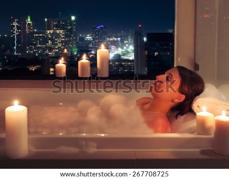 Relaxed woman in bathroom with candles with night city on background - stock photo