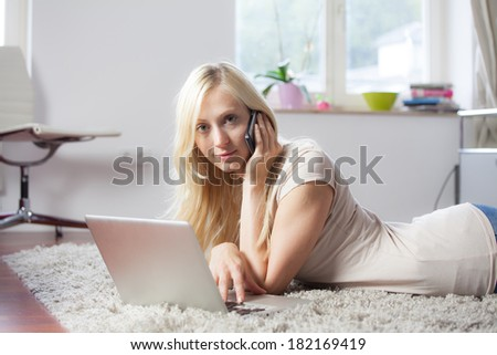 Relaxed woman is using the laptop and telephone in her livingroom, lying on the carpet - stock photo
