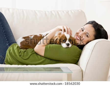 Relaxed woman laying on sofa holding and petting pet dog - stock photo