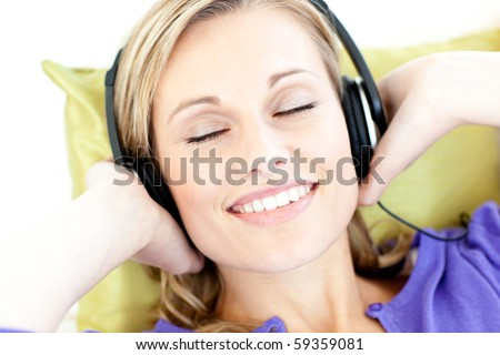 Relaxed woman listening to music in the living-room at home - stock photo
