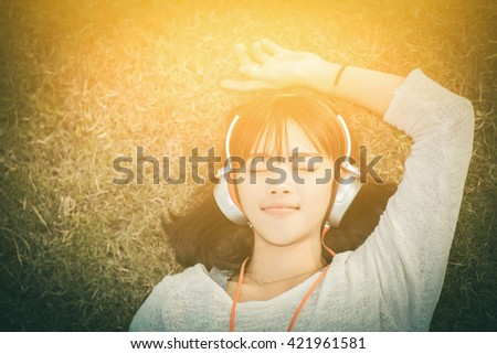 Relaxed woman listening to the music with headphones lying on the grass , sunset  vintage tone - stock photo