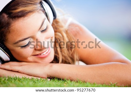 Relaxed woman lying on the floor and listening to music - stock photo