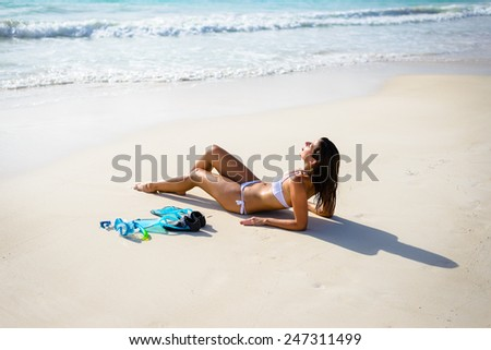 Relaxed woman on tropical beach vacation tanning and resting after snorkeling. Brunette beautiful girl in white bikini relaxing and sunbathing. - stock photo