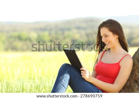 Relaxed woman reading an ebook in the country leaning under a tree shadow wearing a red color shirt - stock photo
