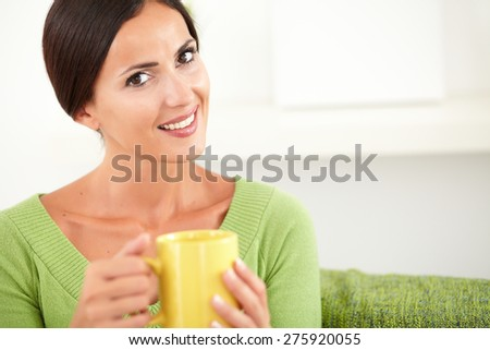 Relaxed woman sitting indoors and looking at the camera with a toothy smile