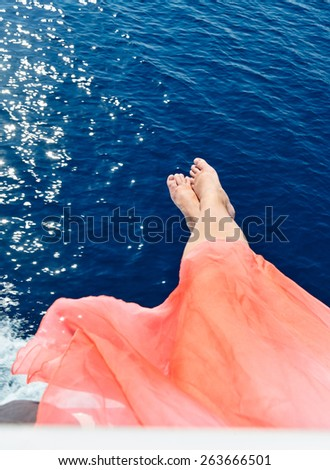 relaxed woman sitting on a sailing boat - stock photo