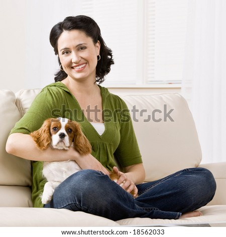 Relaxed woman sitting on sofa holding pet dog - stock photo