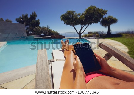 Relaxed woman using digital tablet by the swimming pool. Tanned female model sunbathing and holding tablet PC at poolside.