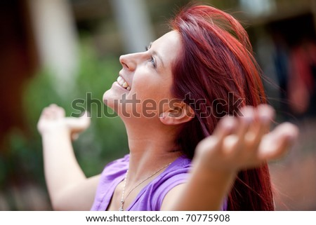 Relaxed woman with arms open outdoors and smiling - stock photo