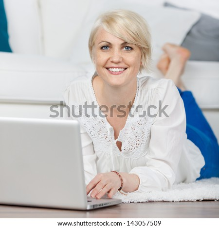 relaxed woman with laptop lying on the floor in living-room