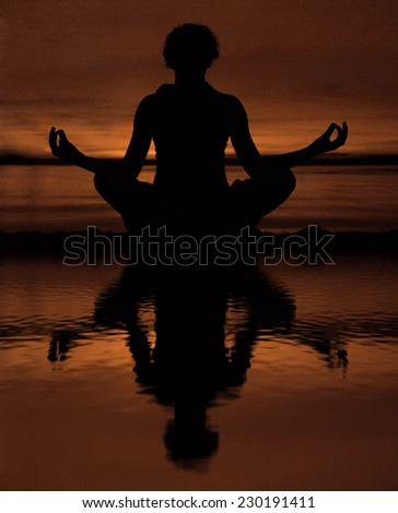 Relaxed Yoga woman or girl sitting in lotus pose on summer sunset beach during yellow and red sun set in bright colors. With reflection in water texture - stock photo