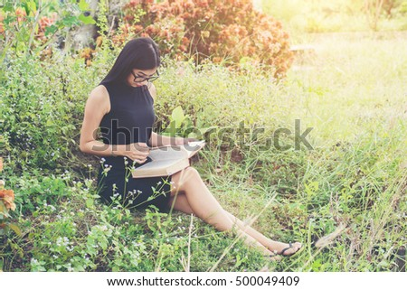 Relaxed young beautiful woman reading a book at the lawn with sun shining.