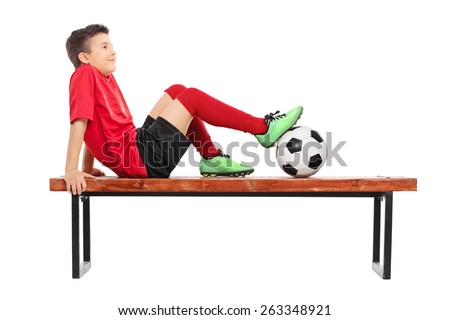Relaxed young boy in football uniform sitting on a wooden bench and thinking isolated on white background - stock photo
