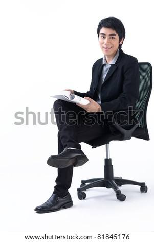 Relaxed young business man holding a magazine - stock photo