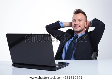 relaxed young business man sitting at his laptop with his hands behind his head and smiling for the camera. on a gray studio backgroud