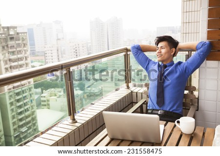 relaxed young business man watching the city view - stock photo