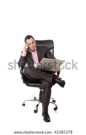 Relaxed young businessman, sitting on a chair with laptop. Isolated on white background. - stock photo