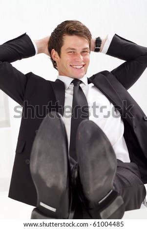 relaxed young businessman with arms behind his head - stock photo