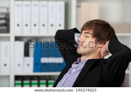 Relaxed young businessman with hands behind head and closed eyes in office - stock photo