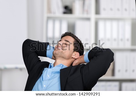 Relaxed young businessman with hands behind head in office - stock photo