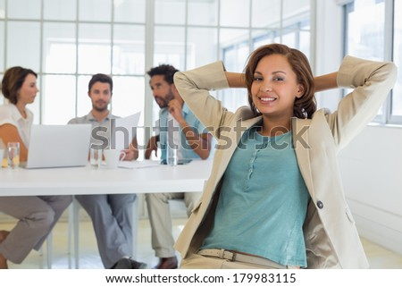 Relaxed young businesswoman with colleagues in meeting in background at the office - stock photo