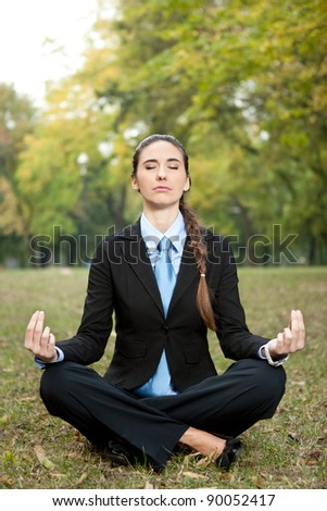 relaxed,  young businesswomen sitting in yoga position on grass - stock photo