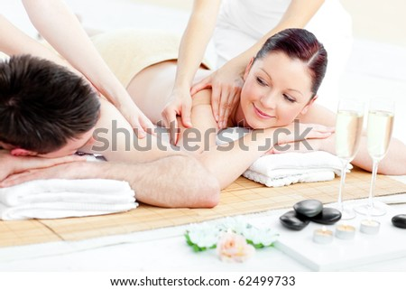 Relaxed young couple enjoying a back massage in a health spa - stock photo