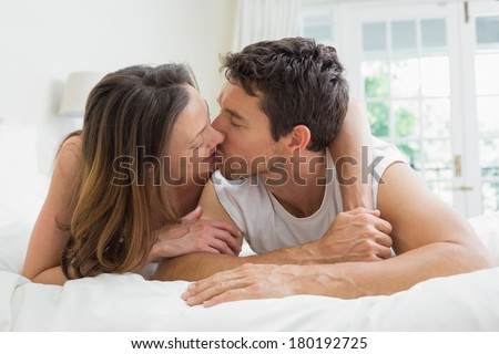 Relaxed young couple kissing in bed at home - stock photo