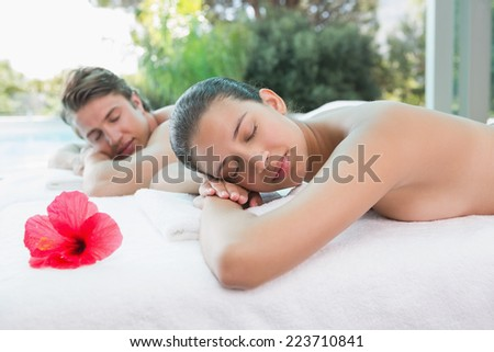 Relaxed young couple lying on massage table at spa center - stock photo