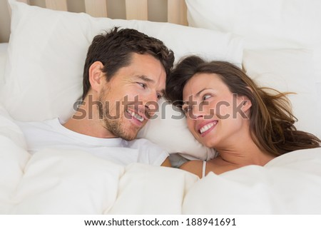 Relaxed young couple lying together in bed at home - stock photo