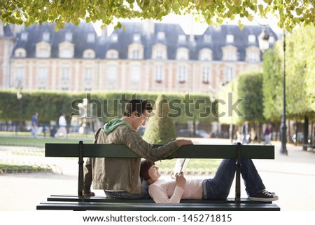 Relaxed young couple reading book on city park bench - stock photo