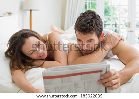 Relaxed young couple reading newspaper in bed at home - stock photo