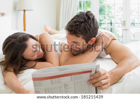 Relaxed young couple reading newspaper in bed at home