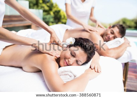 Relaxed young couple receiving a back massage from masseur in a spa - stock photo