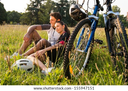 Relaxed Young Couple Sitting In Meadow Near Bicycles  - stock photo