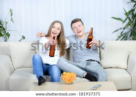 Relaxed young couple watching tv and drinking beer at home in bright living room - stock photo