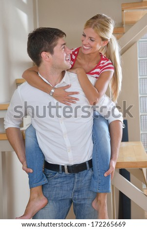 Relaxed young  couple watching tv at home in bright living room - stock photo