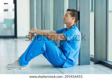 relaxed young doctor sitting on the floor - stock photo