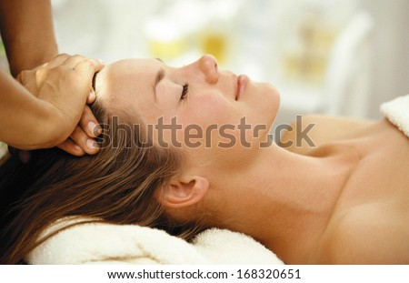 Relaxed young female getting massage in a spa - stock photo
