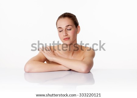 relaxed young female model with eyes closed massaging her shoulders,leaning on white glass for body treatment,studio shot,white background - stock photo