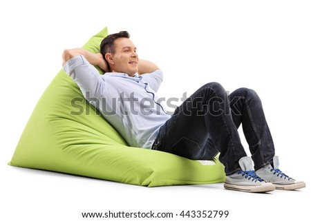 Relaxed young guy laying on a comfortable green beanbag isolated on white background - stock photo
