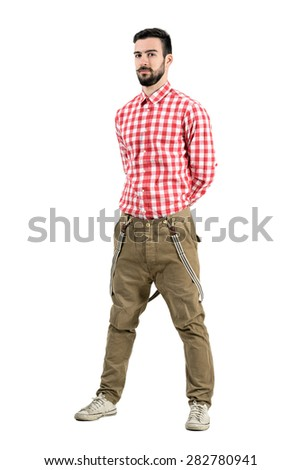 Relaxed young hipster posing with hands on the back. Full body length portrait isolated over white background.