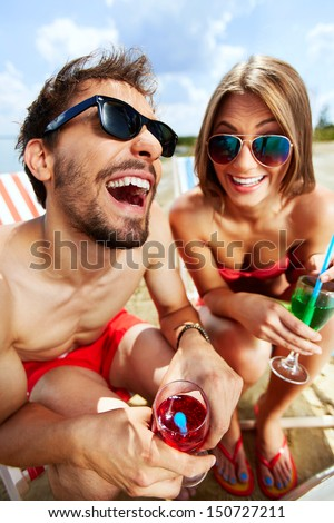 Relaxed young lovers having fun on the beach on a sunny day - stock photo