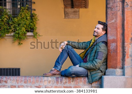 Relaxed young man close up portrait outdoor in the city center of Bologna, Italy.