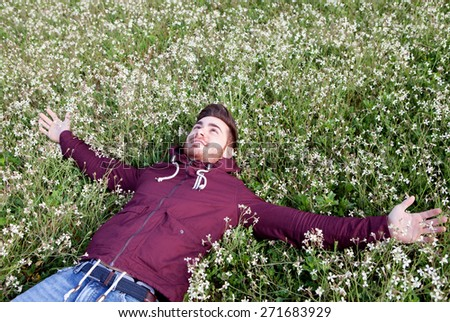 Relaxed young man lying on a field of flowers - stock photo